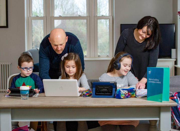 A family of five at a table. Two young girls and a boy sit at it using various devices, while their parents lean over to assist them.