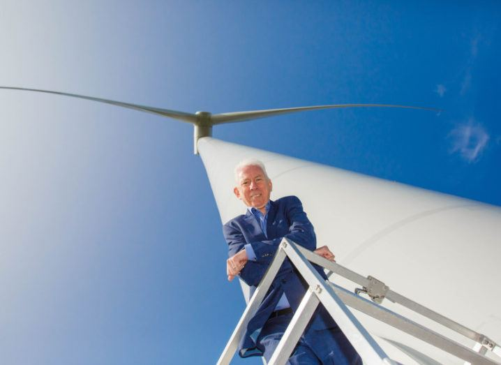Bord na Móna's Tom Donnellan is standing underneath a large wind turbine on a sunny, cloudless day.
