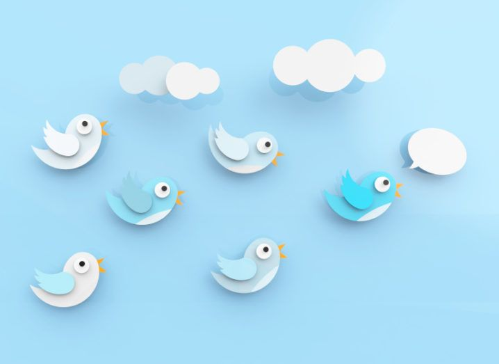 Six paper cut outs of birds in the shape of the Twitter bird logo floating against a blue background. The bird in front has a speech bubble over it.