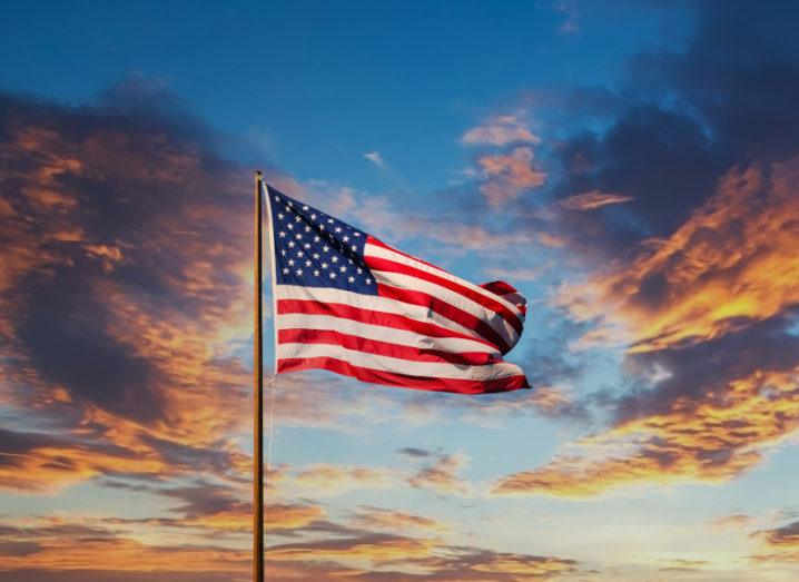 US flag blowing in the wind against a colourful sky at sunset.