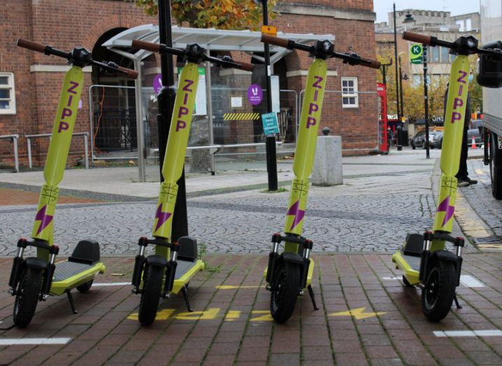 A row of yellow Zipp Mobility scooters are parked on a city street.