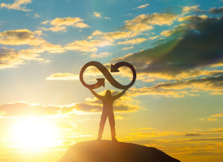 A silhouette of a man standing on a hill against the sunlight. He is holding an infinity symbol in the air, representing a circular economy.