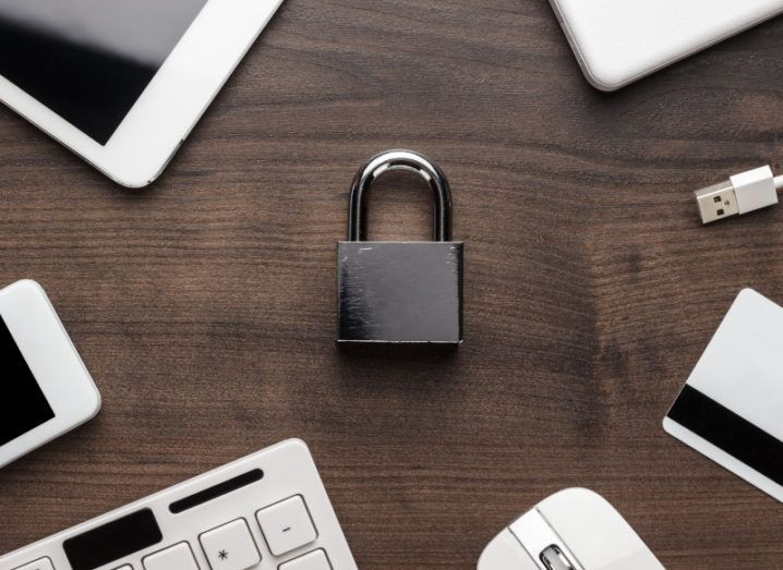 A black shiny padlock lies flat on a dark wooden surface. On the edges of the frame, the lock is surrounded by white electronic devices.