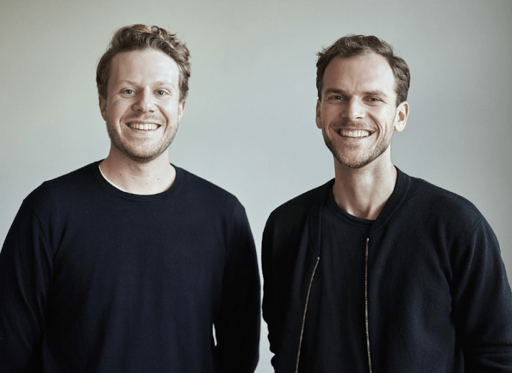 Sebastian Schüller and Jakob Gillmann, founders of HiPeople, wearing black jumpers and smiling at the camera.