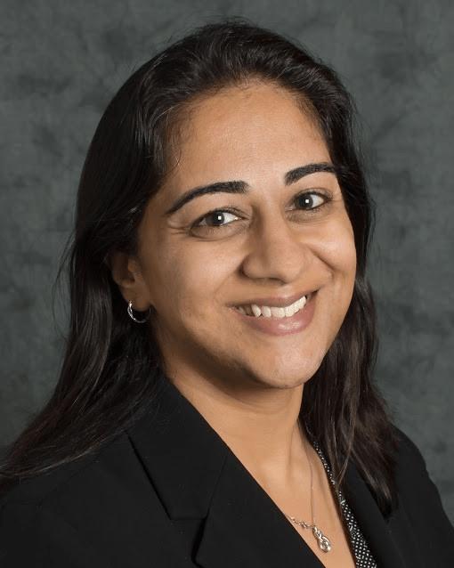 Vidya Krishnan of Ericsson is smiling into the camera against a dark grey background.
