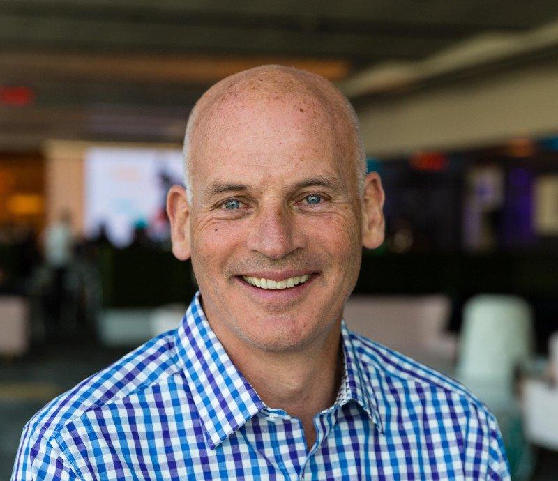 A headshot of John Riordan smiling into the camera and wearing a blue shirt.