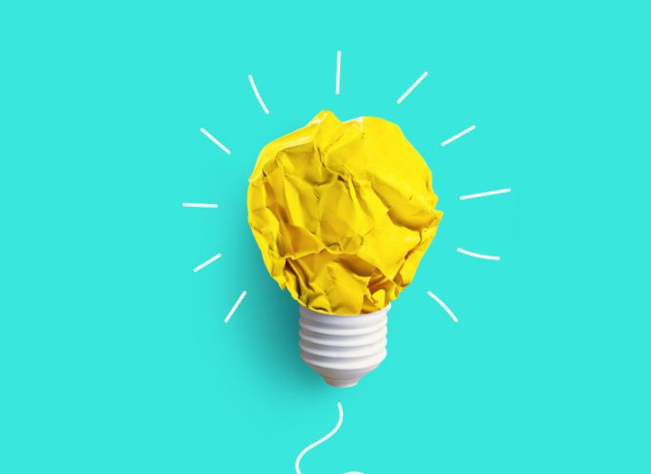 A bright blue background with a lightbulb on it. The bulb itself is made of a scrunched-up piece of yellow paper.