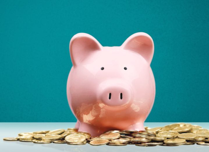 A pink piggy bank sits on a table surrounded by gold coins.