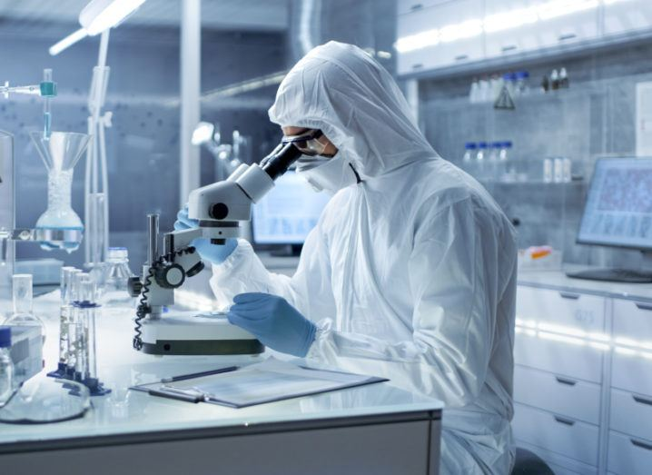 A researcher wearing a protective hooded lab coat sits at a microscope examining a petri dish.