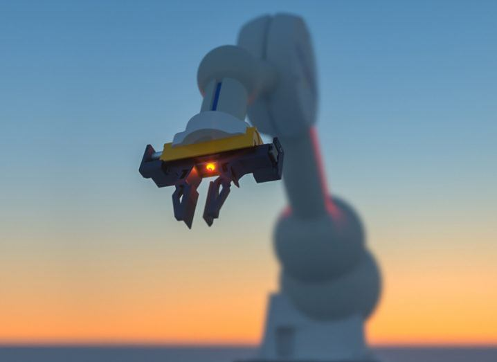 A white robotic arm facing the camera with a small red light on the front against a sunset sky.