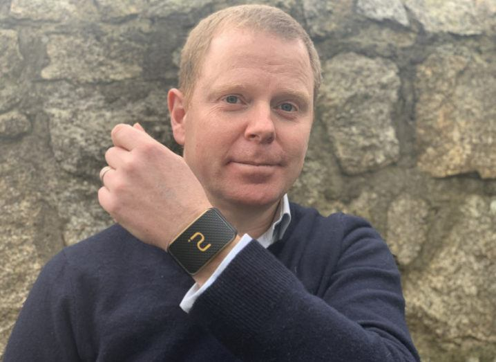 A man holds up his left arm to show he is wearing the Galenband heart monitoring device on his wrist.