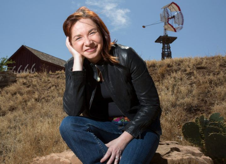 Climate scientist Katharine Hayhoe sits on a rock outside smiling at the camera. A house and a backyard windmill in the background.