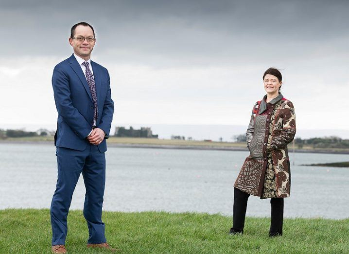 Anthony Cheung and Gillian Buckley stand outside beside a body of water.