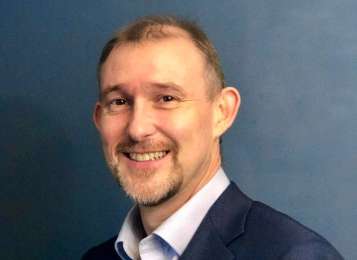 A headshot of Adam Spearing, field CTO for Salesforce EMEA. He's wearing a suit and standing against a blue background.