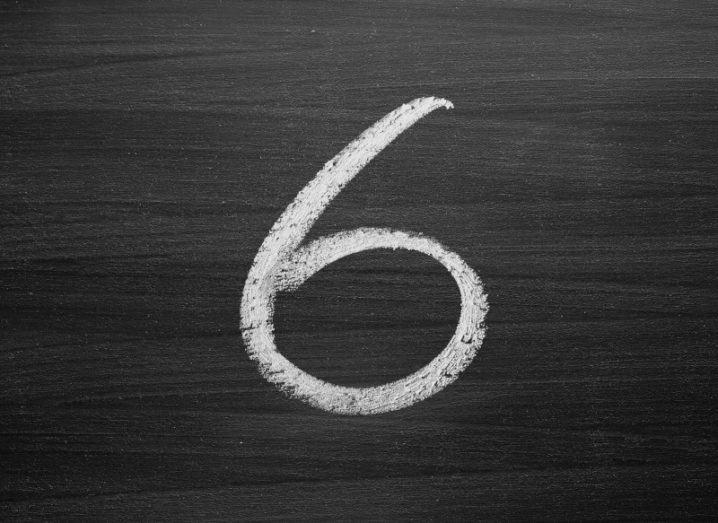 The number six written in white chalk on a blackboard.