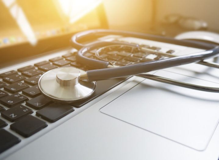 A stethoscope is resting on a laptop.