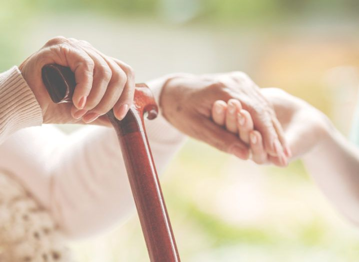 An older woman is holding a walking stick in one hand and a nurse's hand in the other.