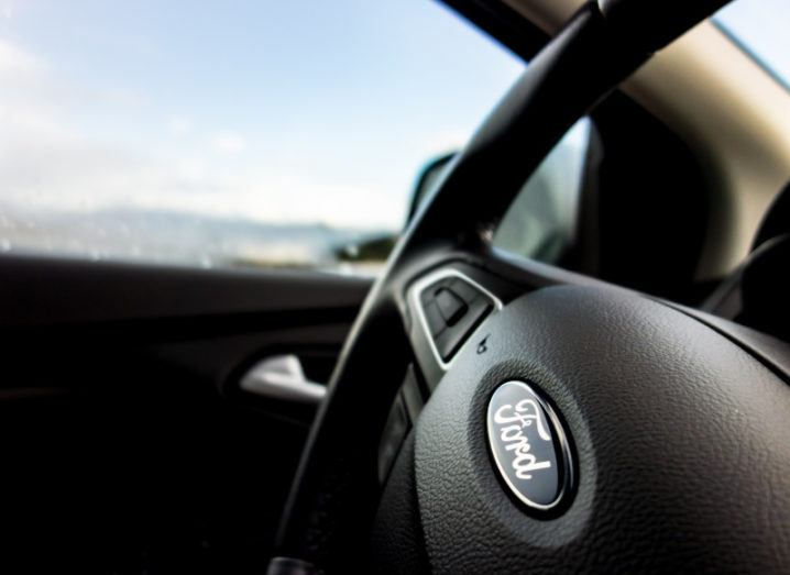 Close-up image of a steering wheel in a car, with the Ford logo on it.