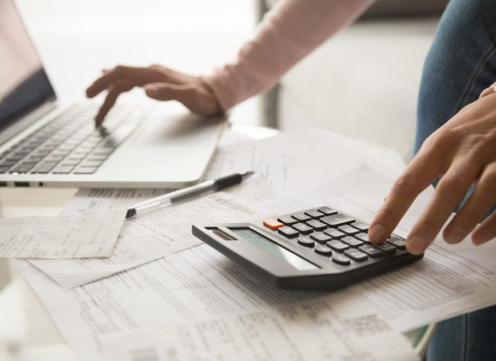 A woman's hands are using a laptop and a calculator, at a desk filled with financial documents.