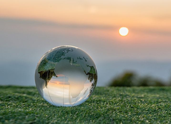 A crystal globe lies in the grass reflecting a sunrise in the distance.