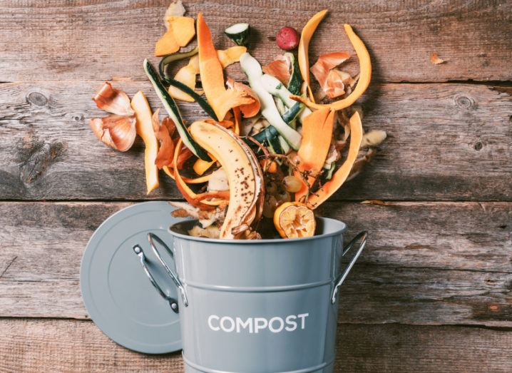 A bucket of food and household waste spilling over onto a wooden floor.