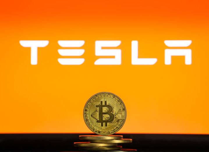 The Tesla logo hovers above a stack of gold coins bearing the bitcoin logo.