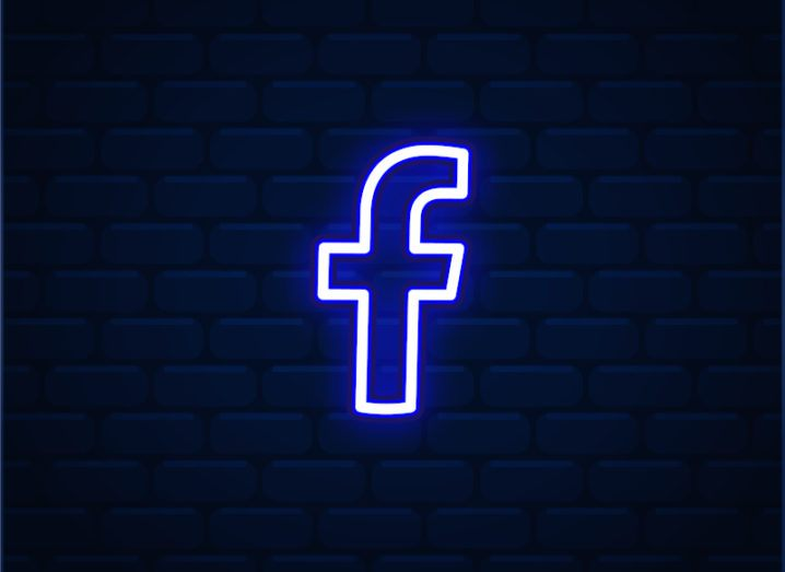 A neon Facebook logo lights up against a darkened brick wall.