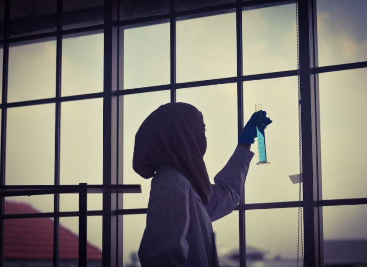 A young woman researcher is holding up a graduated cylinder in a lab with a large window.