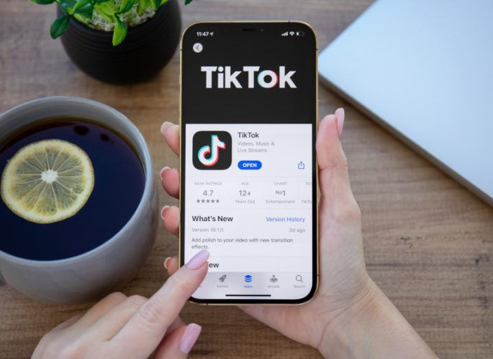 A person is using the TikTok app on a mobile phone above a desk with a cup of tea and a plant.