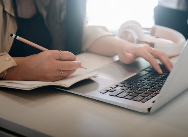 Close-up of a student's hands using a laptop and writing on a notepad.