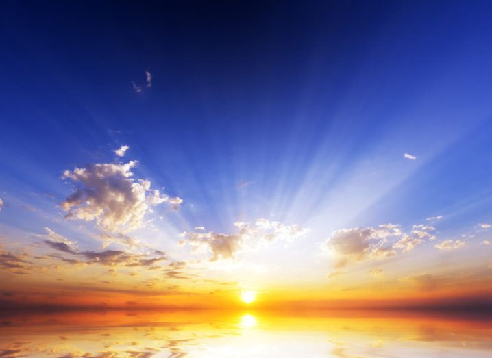 A sun rises over an ocean.