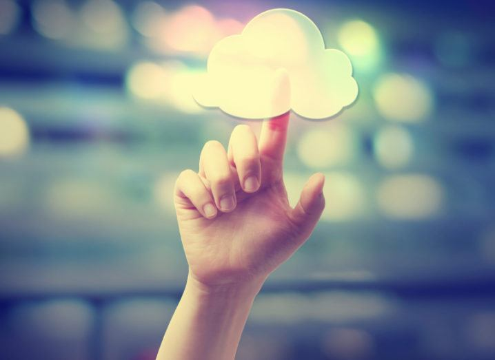 Hand pressing a cloud computing icon on blurred cityscape background.
