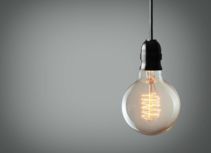 A light bulb is hanging against a plain grey background.