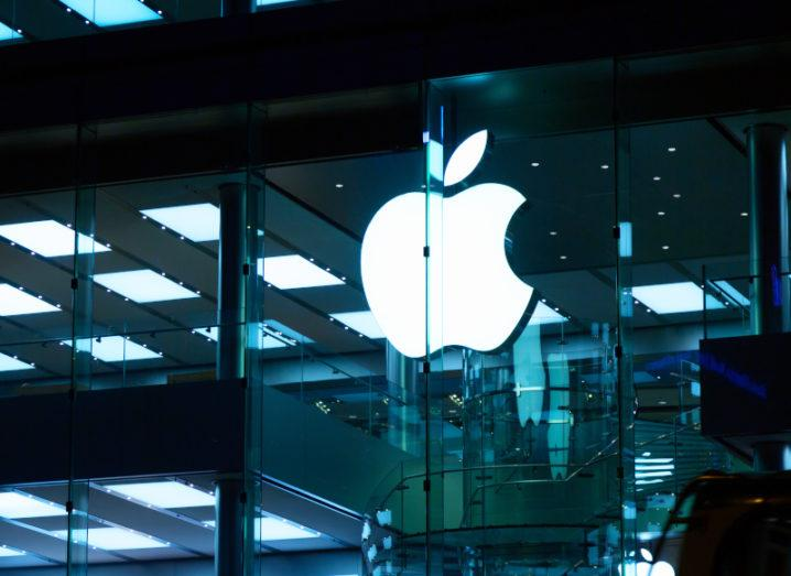 A white, lit-up Apple logo on the outside of a glass building at night.