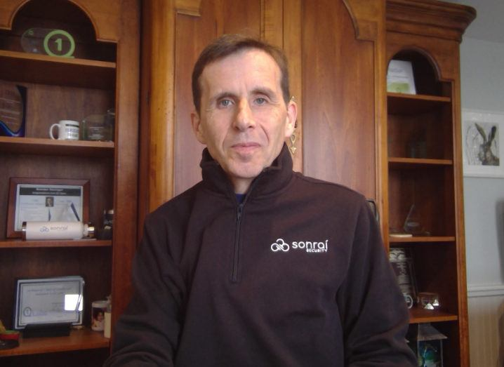 Brendan Hannigan stands in an office wearing a jacket that says 'Sonrai Security' on the front.