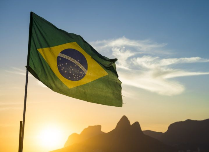 Brazilian flag backlit by a sunset at Ipanema Beach in Rio de Janeiro, Brazil.