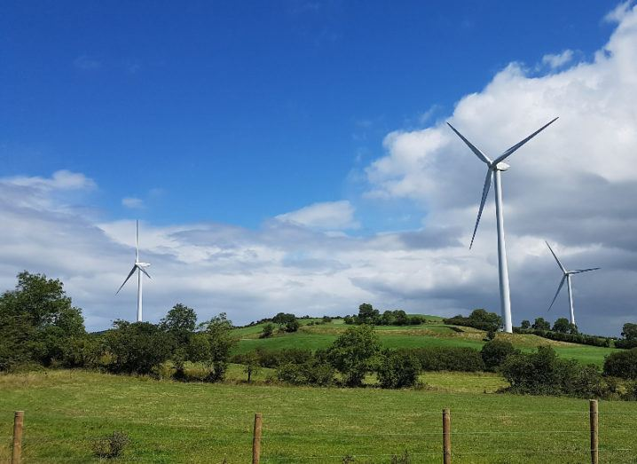 Three wind turbines are in a field on a sunny day.