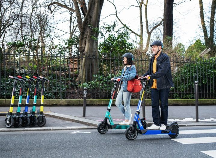 Two people riding on electric scooters