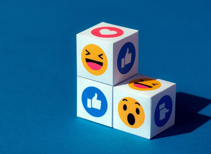Three white cubes stacked against a dark blue background with a number of Facebook emojis on each of the cube sides.