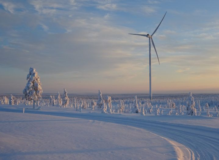 A wind turbine is standing in the middle of a snowy landscape.