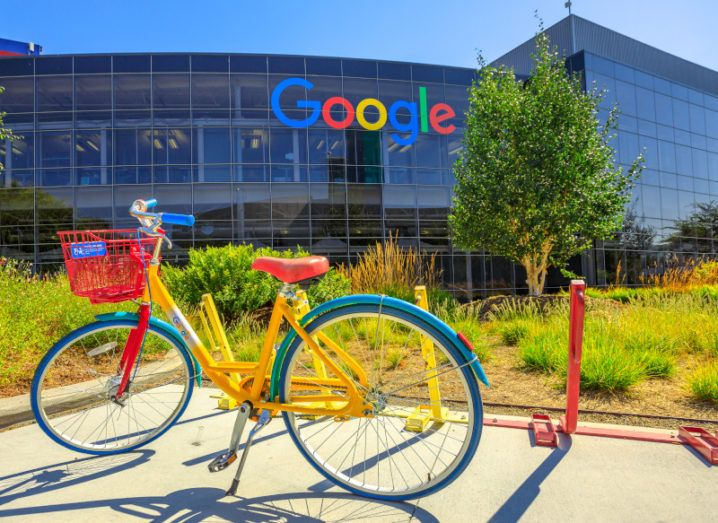 A bicycle in the Google colours sits on a Google campus in front of a large glass building with the company logo on the side.