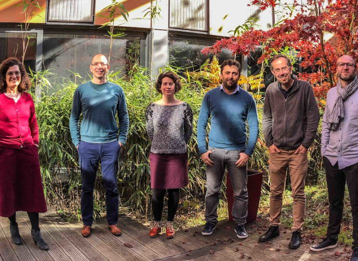 The Grapheal team. Six people stand in a line in smart-casual clothes on wooden decking in front of shrubbery.