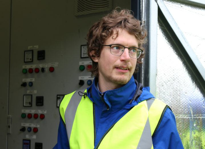 A man in a high-vis jacket stands next to a large industrial control panel.
