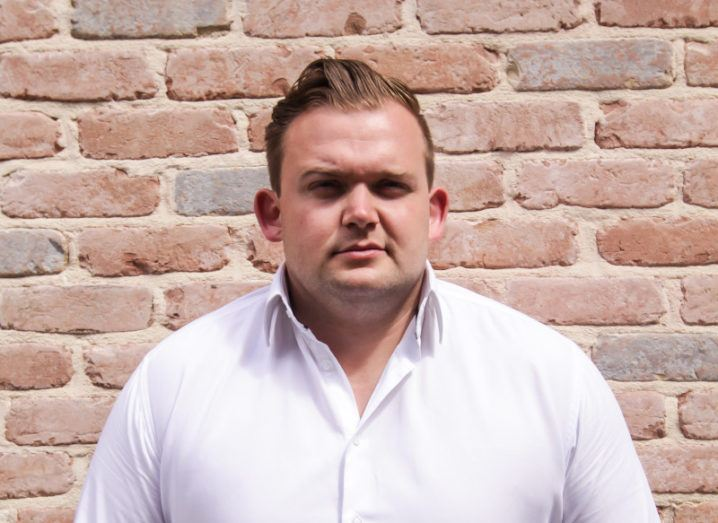 Ivano Cafolla of Zazu Ents is standing against a brick wall wearing a white shirt and looking into the camera.