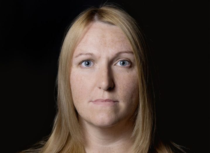 Headshot of Dr Jessica McCarthy, a blonde woman who is standing against a black background.