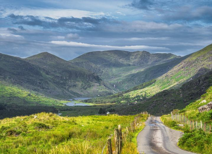Long country road leading to The Black Valley in Co Kerry with lake and mountain range covered in sunlight and shadows from clouds.