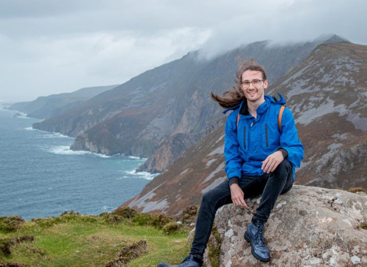 PhD researcher Lorin Sweeney poses by a cliff-edge overlooking the sea.