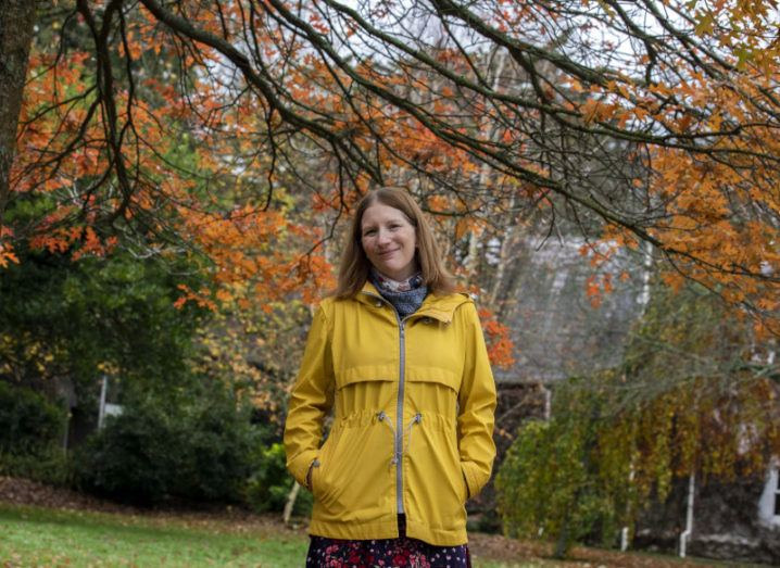 A woman in a floral dress and yellow rain jacket stands with her hands in her pockets in a park where nearby trees' leaves have turned burnt orange.