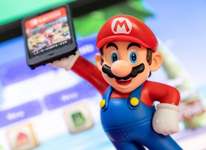 Mario, Nintendo's mascot, holding a game cartridge.