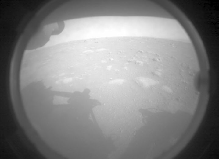 Image of the Mars surface from a Perseverance camera. It shows a grey, rocky surface, with the shadow of the rover.